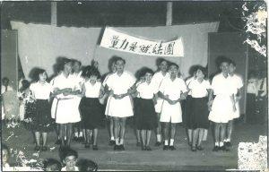 """学生呈现歌唱和舞蹈节目,打起""""团结就是力量""""的布条。"""